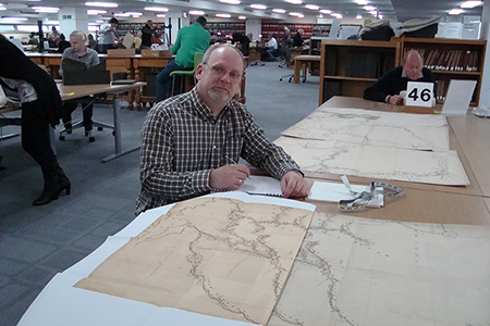 A. Korsos comparing replica map with original. The National Archives, Kew, UK